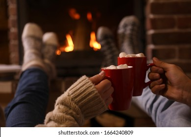 Couple with cups of delicious cocoa resting near fireplace at home, closeup. Winter vacation