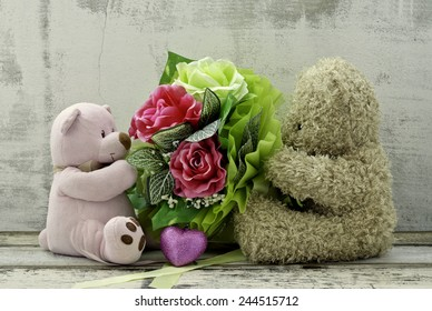 couple of cute  bear dolls holding roses bouquet