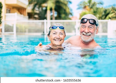 couple of cute seniors and pensioners in the water of the pool having fun and enjoying together - two mature people in love looking at the camera - doing exercise and training together smiling