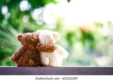 Couple of cute teddy bears are hugging and sitting on blurred green nature background, Love and relationship concept, friend concept