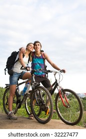 Couple of cyclers on their bikes embracing outdoors during trip
