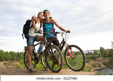 Couple of cyclers on their bikes embracing each other in the countryside