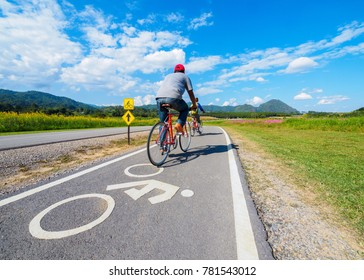 couple cycling red bicycle on bike path along road in Wide field