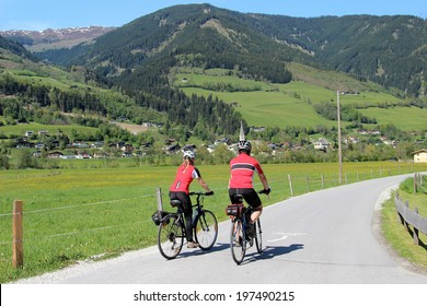 Couple cycling through the valley of the Austrian Alps