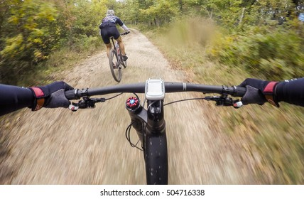 Couple of Cyclists during a mountain bike race in a forest. Drop of water on lens. POV