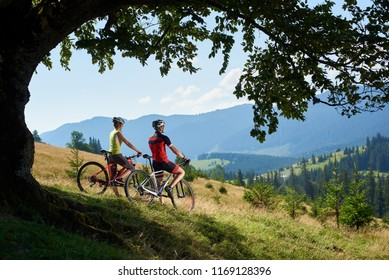 Couple cyclists, man and woman in helmets and full equipment, standing with bicycles on grassy hill under big tree branch, resting after cycling, enjoying view of blue mountain and sky on background