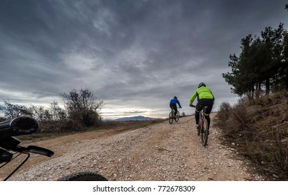 couple of cyclists on a road in the woods in winter