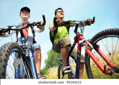 Couple of cyclists riding bicycles in meadow