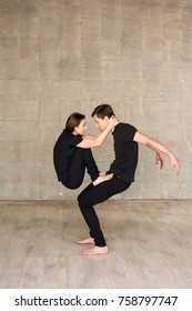 Couple of dancers practicing acrobatics element. Young modern style couple f dancers performing gymnastics element. Artistic and skillful people.