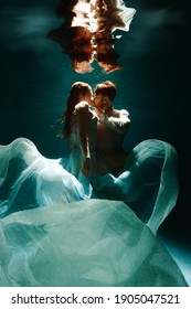 The couple is dancing or hugging in the pool underwater. A girl in a dress with a long train and a guy swim underwater.