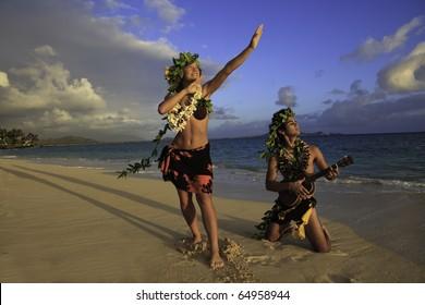 couple dancing hula on the beach at sunrise with the man playing ukulele