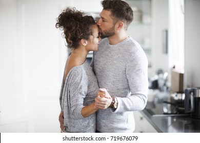 Couple is dancing in the kitchen.