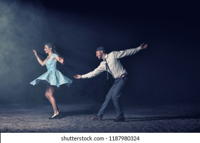 Couple dancing lindy hop at night in front of a spotlight.