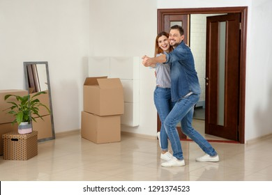 Couple dancing near moving boxes in their new house