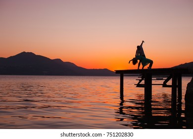 Couple dancing. Silhouette of young happy woman on sunset sea and beach background. Dance man and woman. Fashion photo. Vacation, travel, tourism. Adventure. Sea night background. Summer time. Sensual