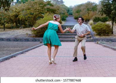 Couple dancing swing lindy-hop in outdoor in the park. People having fun dancing vintage music together in the nature.