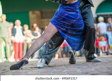 Couple dancing tango in the street among the people