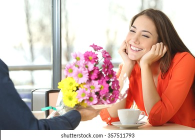 Couple dating and boyfriend giving a bouquet of flowers to his candid girlfriend in a coffee shop
