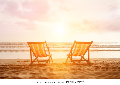 Couple of deck chairs on empty sea beach. Tropical spa resort in exotic country. Vacation travel to Thailand