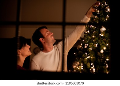 Couple Decorating Christmas Tree in Home, Seen Through Window