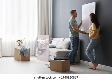Couple decorating room with pictures together. Interior design
