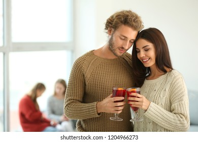 Couple with delicious mulled wine at party
