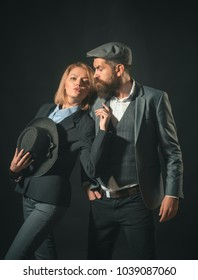 Couple of detectives or researchers, private investigators. Man and woman in retro suit and hat on dark background. Couple in love with suspicious face working together. Private investigator concept.