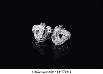 A couple of diamond earrings isolated on Black with reflection