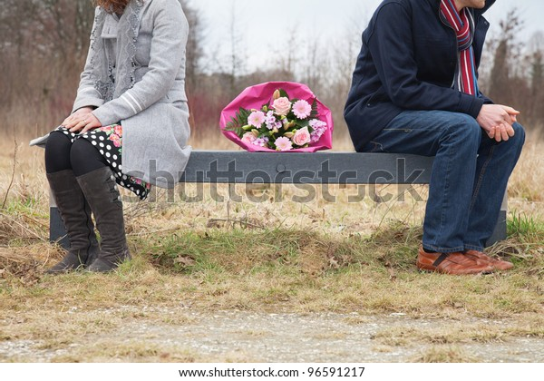 Couple with dificulties sitting on bench with bouquet in between