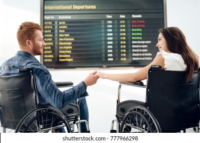 Couple disabled in the airport lounge. A young girl and a guy in wheelchairs near the schedule of flights. Timetable and disabled. Travel disabled at the airport.