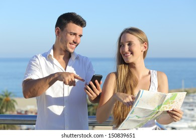 Couple discussing map or smartphone gps on vacations with the sea in the background