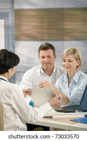 Couple discussing results with physician in doctor's office, smiling.?