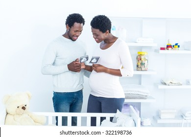 Couple discussing while holding ultrasound scan at home