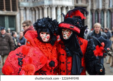 Couple disguised in red black costumes with masks posing in the crowds of tourists during the Carnival in Venice, Italy. The costumes are often hand-made with many accessories. Photo: February 2013