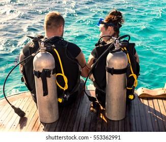 Couple divers preparing to dive, close up.