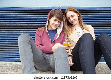 Couple of diverse teenagers together in urban city using smartphone with smiling expressions, fashionable friends outdoors. Adolescents networking technology, leisure recreation lifestyle.