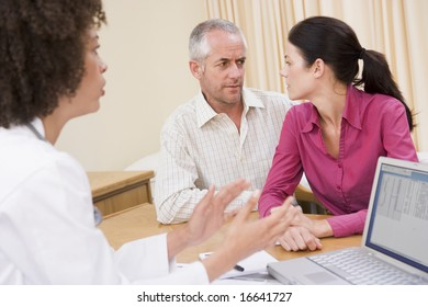 couple and doctor in office looking worried