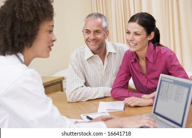 couple and doctor in office smiling