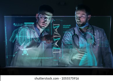 A couple of doctors analyze the patient's medical situation by checking on a glass monitor with a futuristic holography. Concept of: medicine, doctors, future, holography.