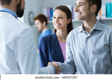Couple at the doctor's office, the doctor is shaking hands with the man, healthcare and consulting concept