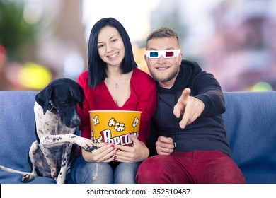 Couple with dog on the couch watching TV