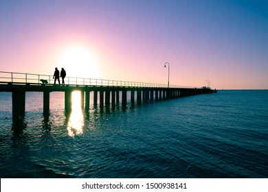 Couple with dog silhouettes on wooden pier at sunset