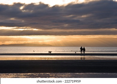 Couple with dogs in silhouette walking on the beach as light rays beam down from the setting sun. White Rock BC, Canada