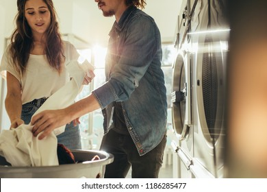 Couple doing laundry together picking clothes from a basket. Couple in a laundry room washing clothes with sun flare in the background.