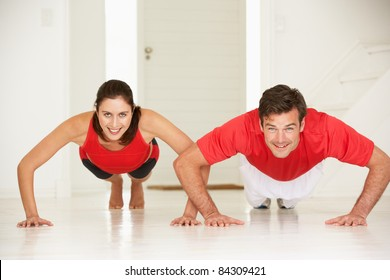 Couple doing push-ups in home gym