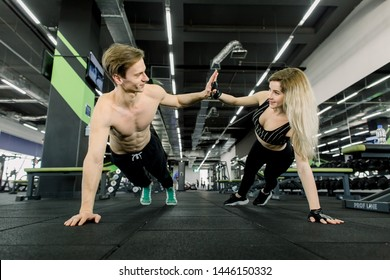 Couple doing pushups at training in gym. Young sporty couple working out together in a gym . Doing plank exercises while holding each other for one hand.