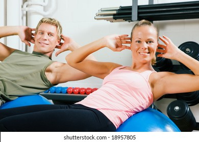 Couple doing situps on a fitness ball as training in the gym
