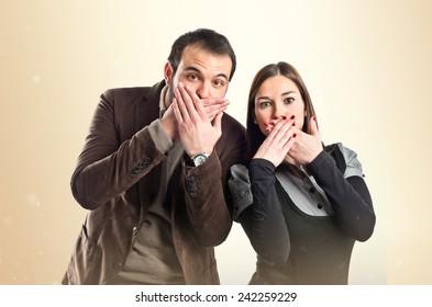 Couple doing surprise gesture over ocher background