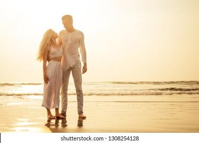 Couple doing yoga exercises on the beach namaste breathing practice tantra yoga