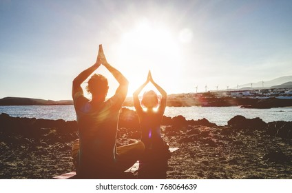 Couple doing yoga outdoor at sunrise in nature - Woman and man meditating together at morning time - Concept of fitness exercise for healthy lifestyle and positive mind - Main focus on man silhouette
